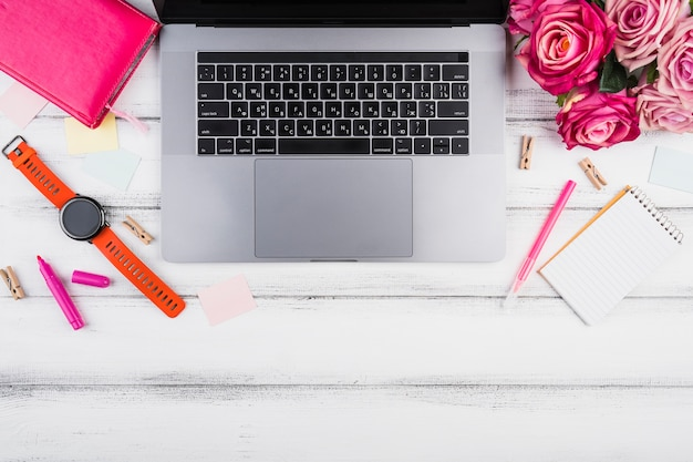 Computer portatile piatto con mazzo di rose rosa