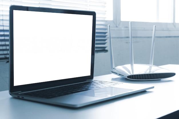 Computer portatile schermo vuoto e dispositivo router sul tavolo
