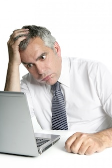 Computer portatile senior sollecitato del lavoro di gesto dell'uomo d'affari