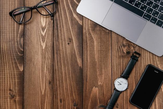 Computer portatile, smart phone, occhiali e orologio sul tavolo di legno.