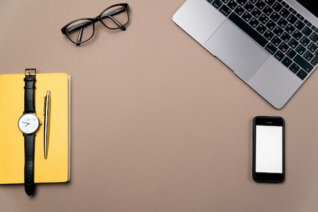 Computer portatile, smart phone, occhiali e orologio sulla scrivania marrone.