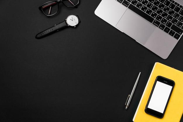 Computer portatile, smartphone, occhiali e orologio sulla scrivania nera.