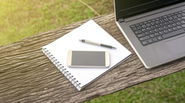 Computer portatile, smartphone, penna e libro sulla tavola di legno.