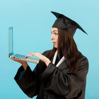 Computer portatile sorpreso della tenuta della ragazza