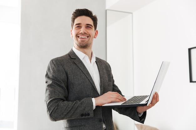 Computer portatile sorridente della tenuta dell'uomo di affari mentre distogliendo lo sguardo