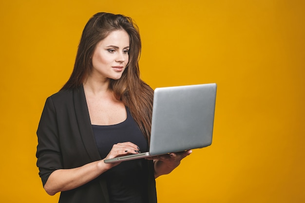 Computer portatile sorridente felice della tenuta della donna di giovani affari ed inviare email al suo migliore amico.