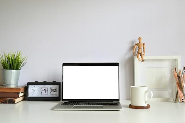 Computer portatile su area di lavoro con schermo vuoto.
