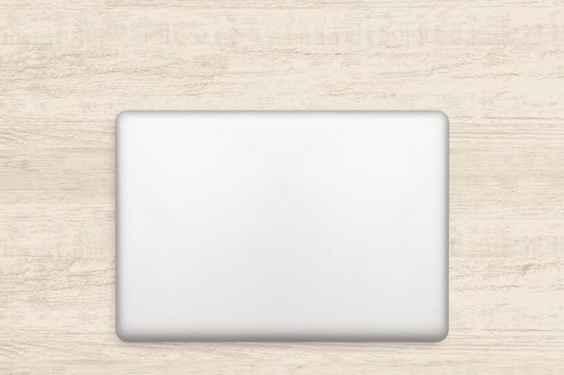 Computer portatile su fondo di legno bianco.