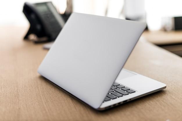 Computer portatile su tavola di legno e sfondo sfocato