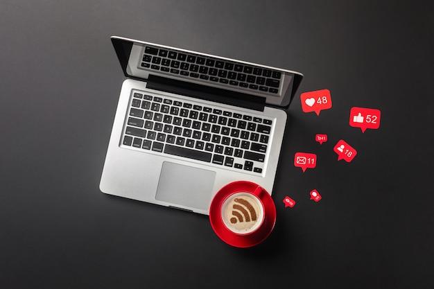 Computer portatile su un desktop nero con una tazza di caffè, un telefono e un segno wi-fi, funziona nei social network. vista dall'alto