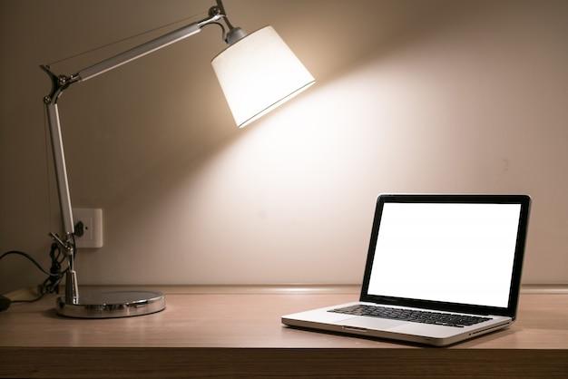 Computer portatile su una scrivania con lampada