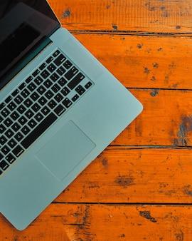 Computer portatile sul fondo della tavola dell'ufficio.