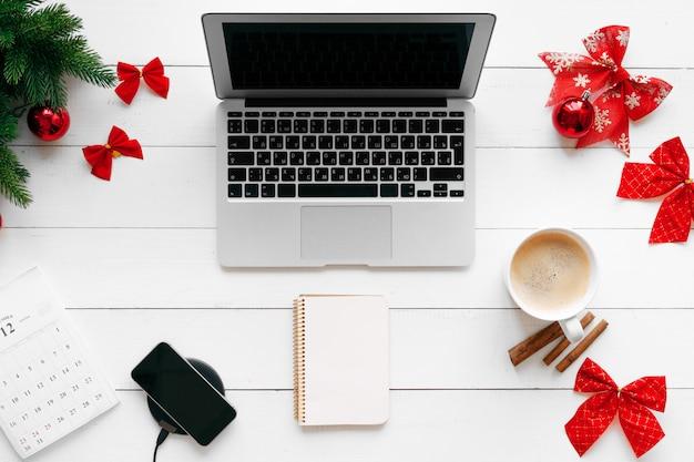 Computer portatile sullo scrittorio di legno bianco circondato con le decorazioni rosse di natale, vista superiore