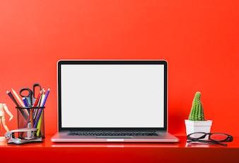 Computer portatile sullo scrittorio rosso con le cartolerie e la pianta del cactus