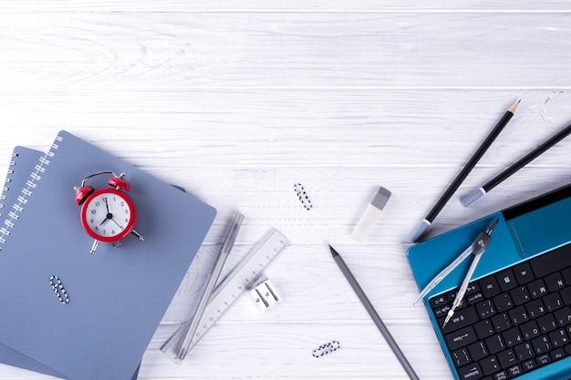 Computer portatile, sveglia rossa e rifornimenti