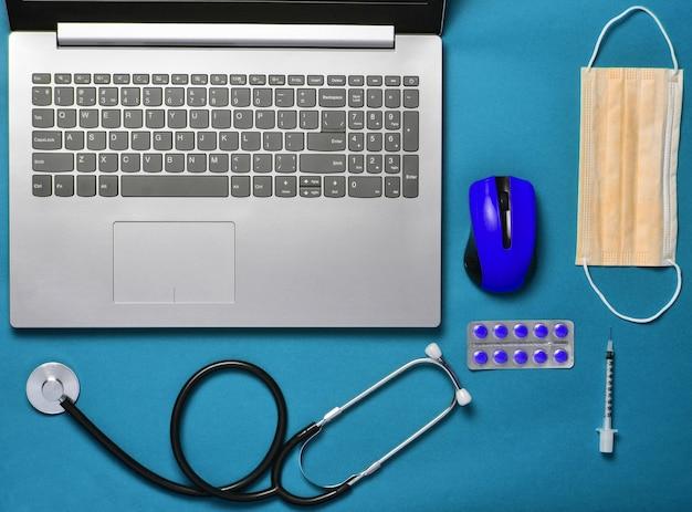 Computer portatile, topo senza fili, taccuino, stetoscopio, pillole su fondo blu