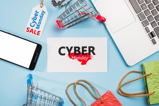 Computer portatile vicino a smartphone, cartellini, carrelli per la spesa e pacchetti