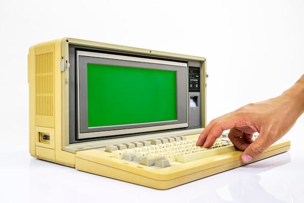 Computer portatili molto vecchi e schermo monitor verde hanno la mano per entrare nella tastiera