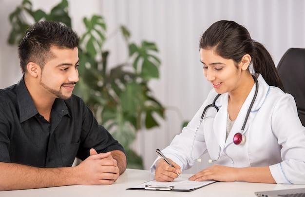 Comunicazione del medico indiano femminile con pazienti maschi