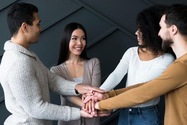 Comunità di giovani che tengono le mani