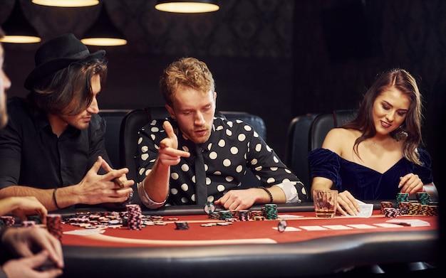 Con bicchieri di bibita. gruppo di giovani eleganti che giocano a poker nel casinò insieme