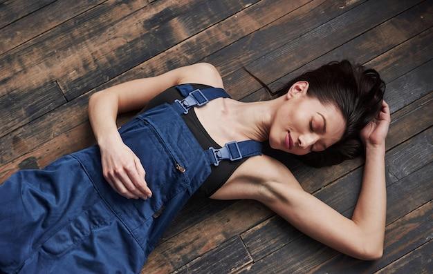 Con gli occhi chiusi. la ragazza con la divisa blu per il lavoro è sdraiata sul pavimento di legno per rilassarsi