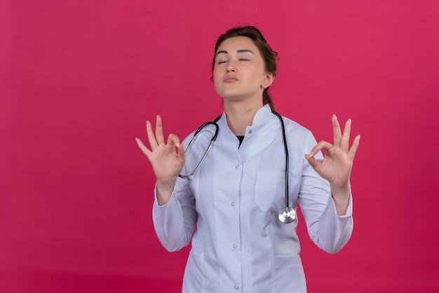 Con gli occhi chiusi medico giovane ragazza indossa abito medico e uno stetoscopio che mostra il gesto di pace su sfondo rosso parassita