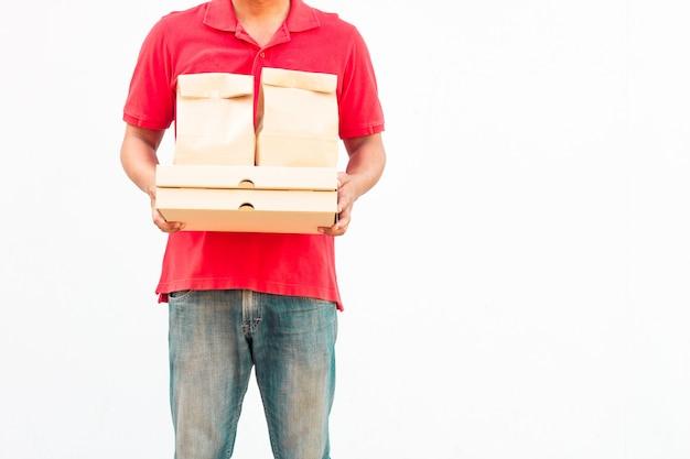 Con in mano vari contenitori per alimenti da asporto, scatola per pizza, supporto e sacchetto di carta, primo piano. sfondo grigio chiaro, posto per inserire il testo. fattorino.