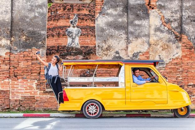 Con in piedi in taxi o tuk tuk e divertimento felice con lo sfondo del vecchio tempio (wat mahathat)