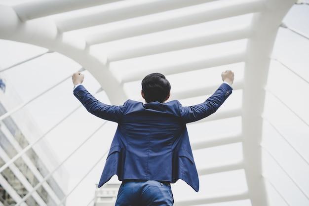 Con successo di giovane uomo d'affari che tiene le braccia alzate e che esprime positività mentre stando all'aperto