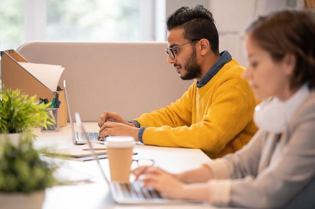 Concentrarsi sul serio giovane uomo mediorientale in maglione giallo seduto al tavolo e preparare la presentazione sul computer portatile