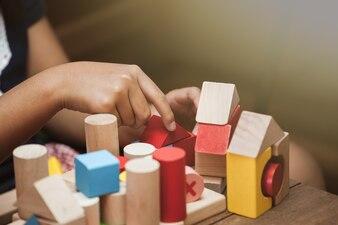 Concentrarsi sulla mano del bambino giocando con blocchi di legno colorati in tonalità di colore vintage