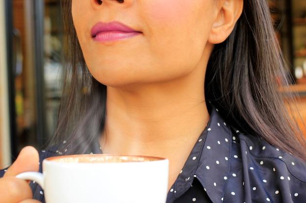 Concentrati sulle labbra di una giovane donna che ama bere caffè caldo.