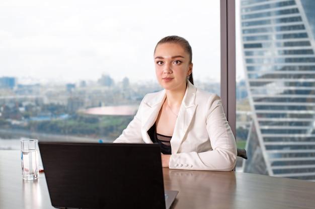 Concentrato al lavoro. giovane donna sicura nell'abbigliamento casual astuto che lavora al computer portatile mentre sedendosi vicino alla finestra in ufficio creativo
