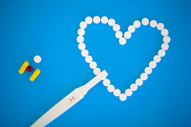 Concep di pianificazione della gravidanza. test di gravidanza positivo con due strisce e pillola contraccettiva