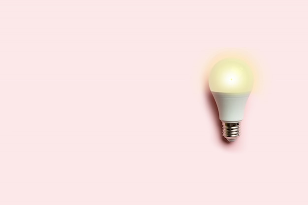 Concept creativo di una lampadina a risparmio energetico luminosa su sfondo rosa. risparmio energetico o idea