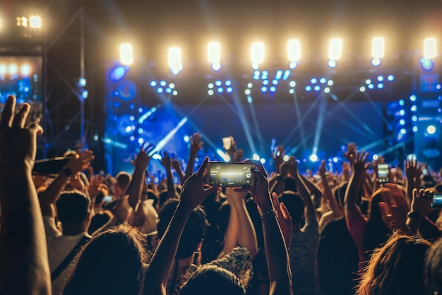 Concerti la folla della mano del fanclub di musica facendo uso del cellulare che prende l'annotazione del video o lo streaming in tensione