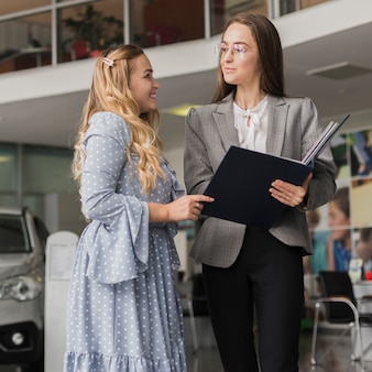 Concessionario auto parlando con donna bionda