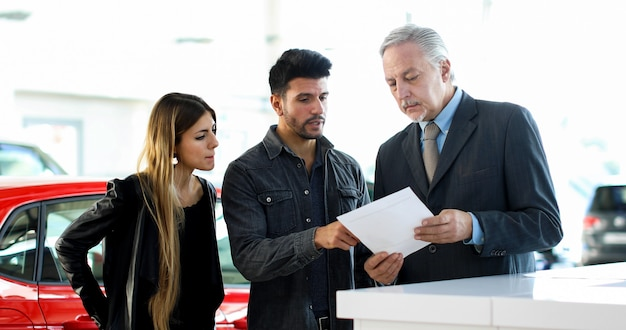 Concessionario di auto che legge un contratto per una coppia in uno showroom automobilistico