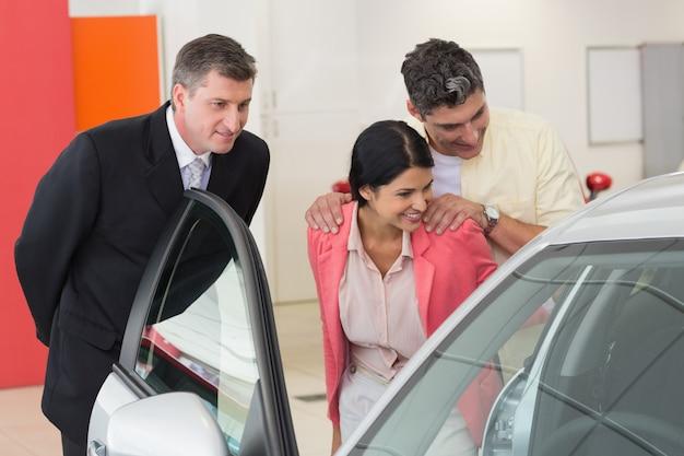 Concessionario di auto che mostra l'interno di una macchina per una coppia
