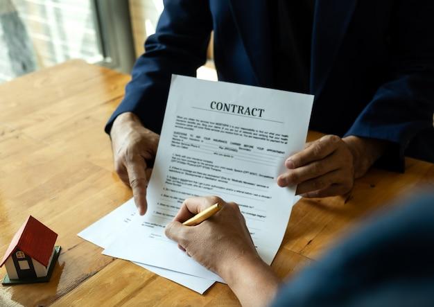 Concetti aziendali, gli uomini d'affari indicano i documenti che i clienti devono firmare.