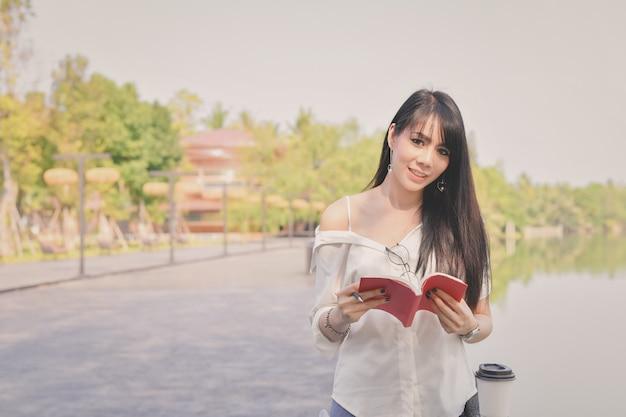 Concetti di educazione. donne asiatiche che leggono libri nel parco.