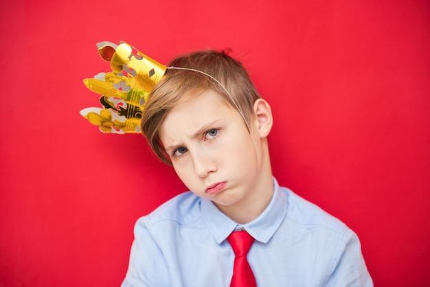 Concetti di educazione e infanzia con un adorabile ragazzo adolescente in possesso di un re d'oro corona in testa