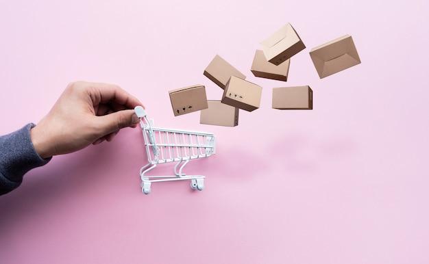 Concetti di shopping online con persona e piccolo carrello e confezione del prodotto
