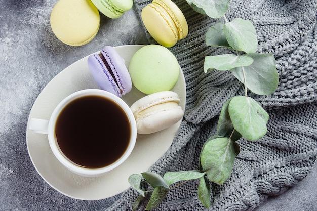 Concetto accogliente mattina. deliziosi macarons colorati pastello con crema e caffè, caldo maglione grigio