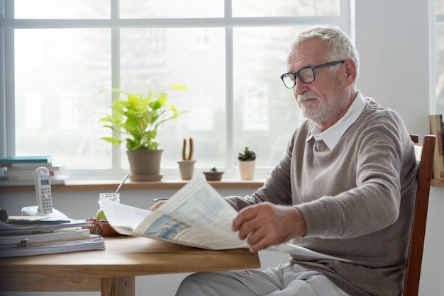 Concetto adulto senior di svago del giornale della lettura