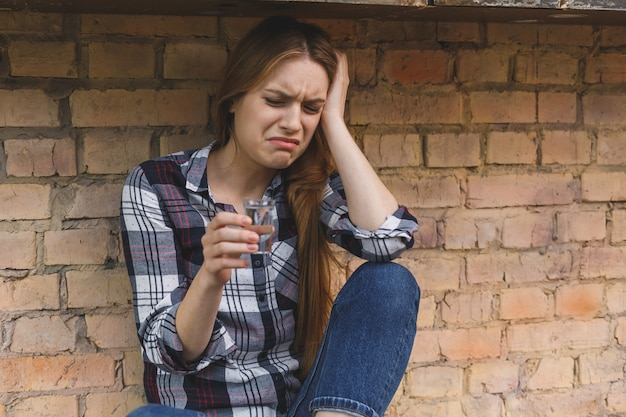 Concetto alcolico di problemi sociali della giovane donna che si siede con gli occhi chiusi in cucina. depressione giovane femmina adolescente avendo abusato del problema sentirsi soffrire e piangere.