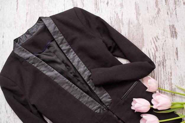 Concetto alla moda. giacca classica nera e tulipani rosa.