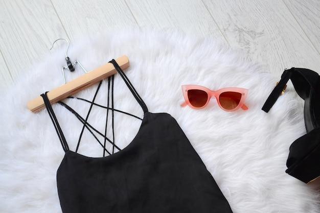 Concetto alla moda, un abito nero e occhiali da sole rosa sulla pelliccia bianca. vista dall'alto