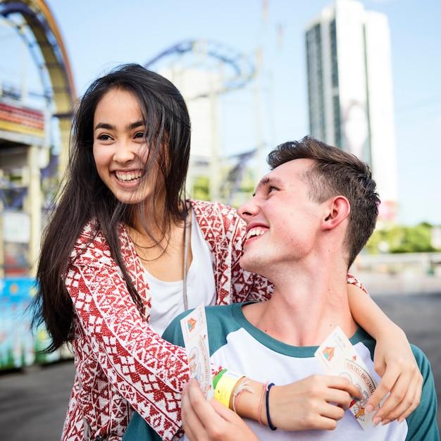 Concetto allegro festivo di felicità della funfair del parco di divertimenti di datazione delle coppie